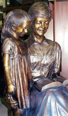 Custom lifesize bronze sculpture scenes, teacher reading to children bronze, Wilson Public Library, Cozad Nebraska, public monumental portrait bronze statues by Tom White, monumental bronze sculptor, statues of children, bronze monuments, public library sculptures, statues for schools of teachers and children